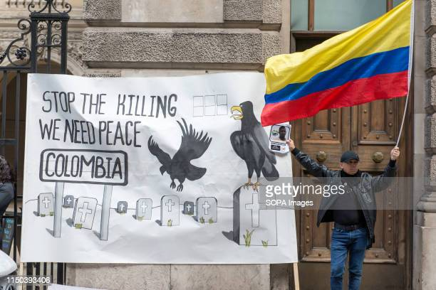 Demonstrator holds a Colombian flag next to a banner during the protest Demonstrators gathered outside Gibson Hall to protest against Colombian...
