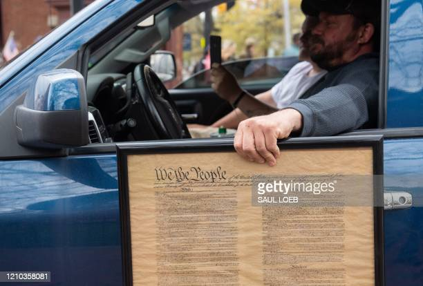 """Demonstrator holds a copy of the US Constitution as he protests during a """"Reopen Maryland"""" rally outside the State House in Annapolis, Maryland,..."""