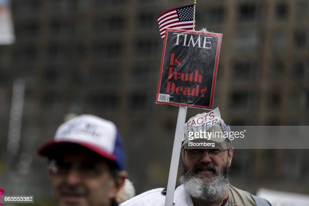 A demonstrator holds a copy of Time Inc's magazine with a cover that reads 'Is Truth Dead' during The People's Filibuster rally at Foley Square in...