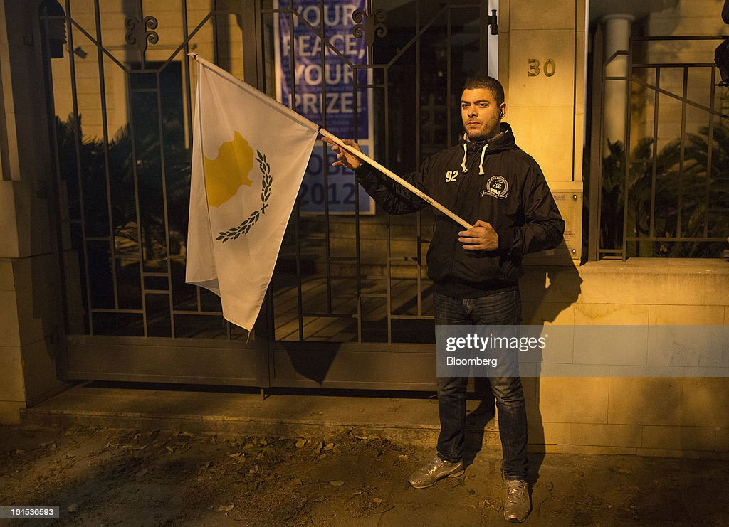 A demonstrator holds a Cypriot flag during a protest outside the European Union House in Nicosia, Cyprus, on Sunday, March 24, 2013. Cyprus's fate hangs in the balance as euro-area finance ministers meet today to decide whether the tiny Mediterranean island has done enough for a bailout that will avert its financial collapse. Photographer: Simon Dawson/Bloomberg via Getty Images