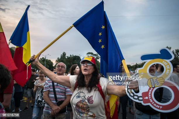 A demonstrator holds a European flag and a cardboard cutout of handcuffs during a gathering in front of the Romanian Prime Minister's office building...