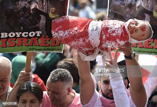 A demonstrator holds a fake child wrapped in a bloody sheet referring to Palestinian children killed during Israel's raids during a demonstration in...