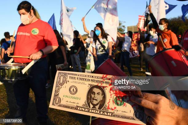 Demonstrator holds a fake dollar bill depicting Brazilian Presidnet Jair Bolsonaro's face and tinted in red as blood during a protest outside the...