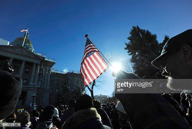 A demonstrator holds a flag during a protest outside the Colorado Capitol building in Denver Colorado on December 19 2016 to demonstrate against US...