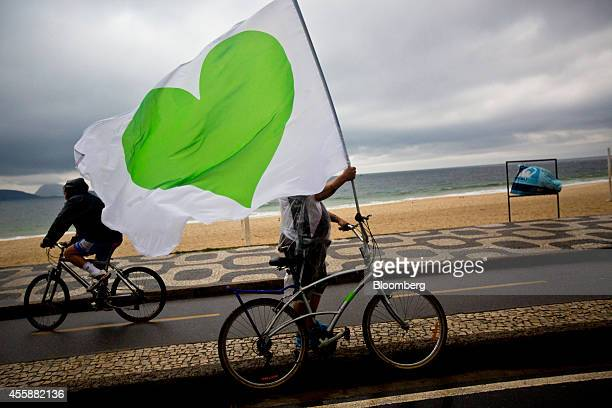 A demonstrator holds a flag during an event held in solidarity with New York City's People's Climate March in Rio de Janeiro Brazil on Sunday Sept 21...