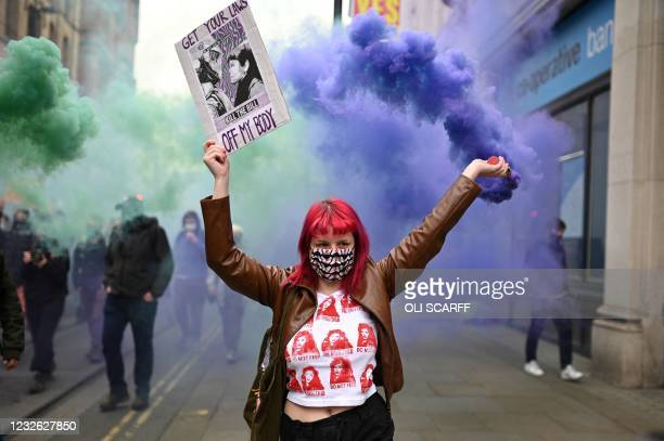 Demonstrator holds a flare and a placard as she protests against the Police, Crime, Sentencing and Courts Bill 2021 in central Manchester on May 1,...
