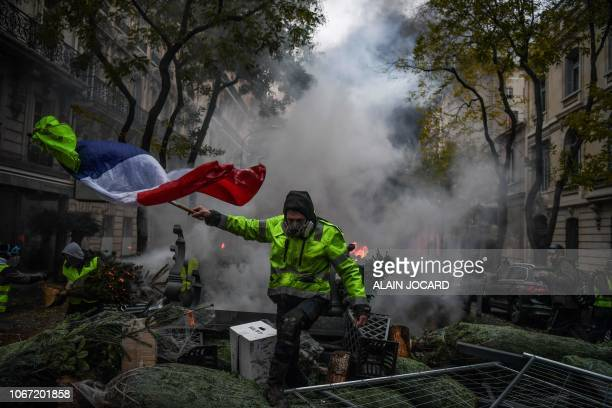 Demonstrator holds a french flag among christmas trees during a protest of Yellow vests against rising oil prices and living costs, on December 1,...