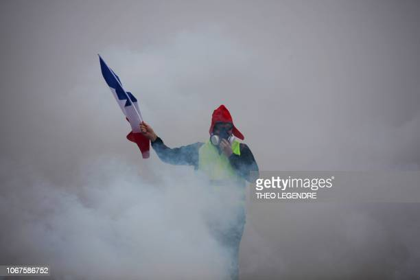 TOPSHOT A demonstrator holds a French flag as he walks amid the tear gas during a protest of Yellow vests against rising oil prices and living costs...
