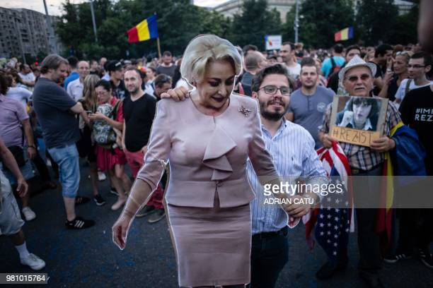A demonstrator holds a fullsize cardboard cutout depicting Romania's Prime Minister Viorica Dancila during a gathering in front of the Romanian Prime...