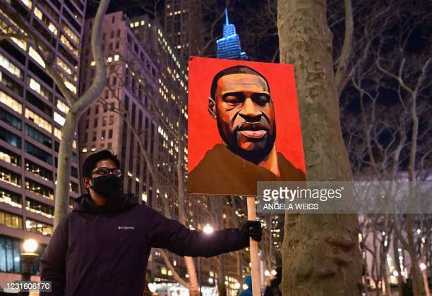 Demonstrator holds a George Floyd placard during a rally on the first day of trial of former police officer Derek Chauvin on March 8, 2021 in New...