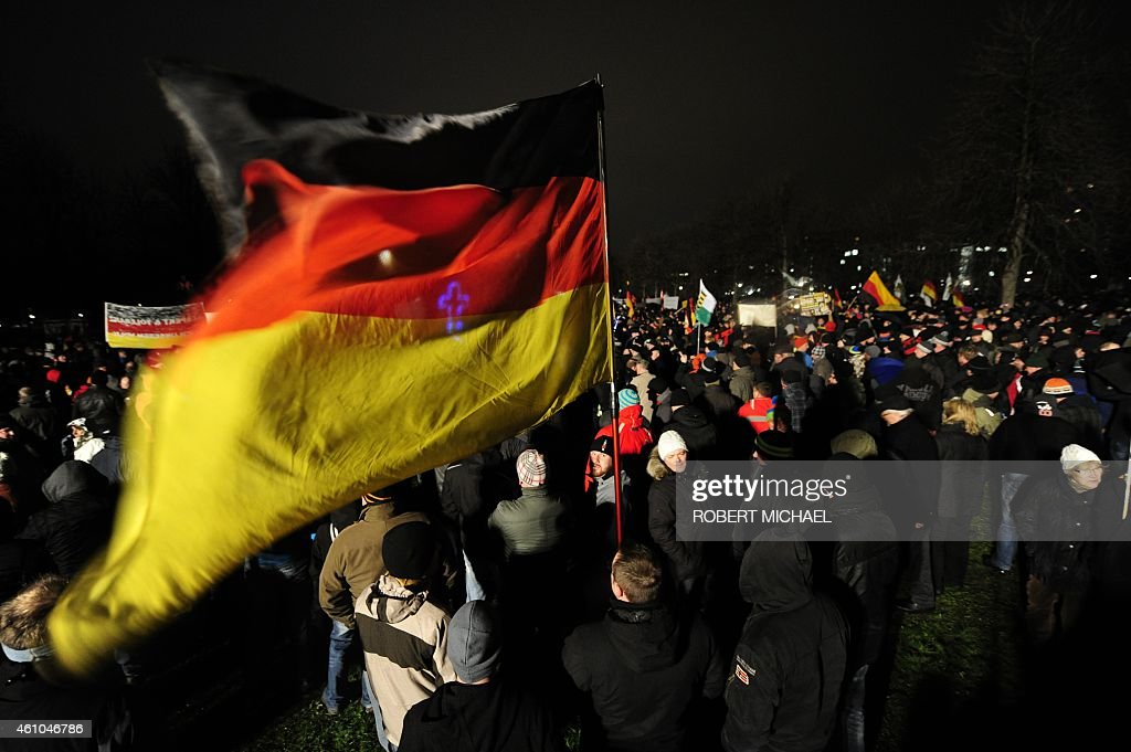 A demonstrator holds a German flag during a rally by a mounting right-wing populist movement on January 5, 2015 in Dresden, eastern Germany. Counter-demonstrations were called for several cities against the group 'Patriotic Europeans Against the Islamisation of the Occident', or PEGIDA, whose weekly anti-immigrant street protests have been condemned by church, business and political leaders.