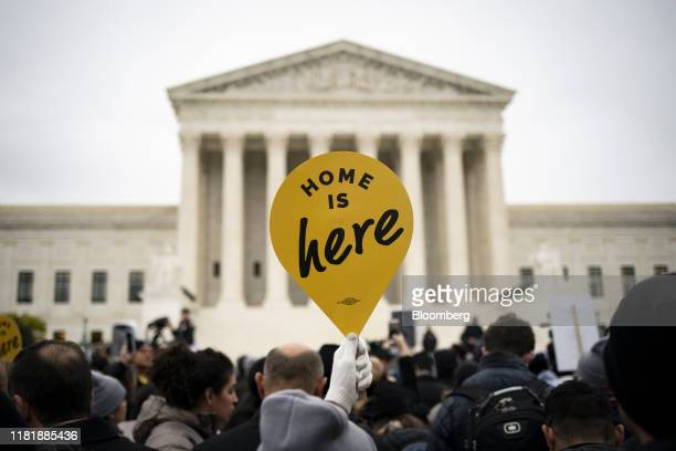 A demonstrator holds a Home Is Here sign during a rally supporting the Deferred Action for Childhood Arrivals program outside of the Supreme Court in...