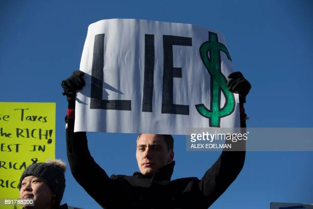 TOPSHOT A demonstrator holds a 'Lie$' protest sign during a demonstration against Republican led tax reform outside the US Capitol in Washington DC...