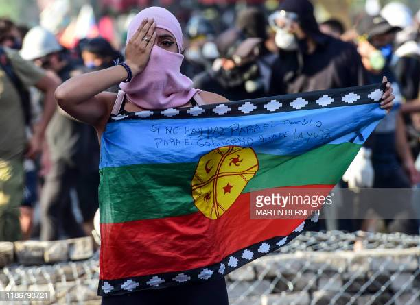 TOPSHOT A demonstrator holds a Mapuche indigenous flag as she covers an eye making reference to demonstrators reached by police pellets in their eyes...
