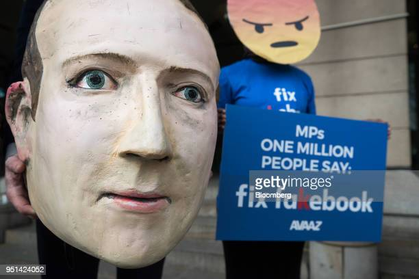 A demonstrator holds a mask depicting Facebook Inc Chief Executive Officer Mark Zuckerberg left as he stands with a demonstrator wearing an angry...
