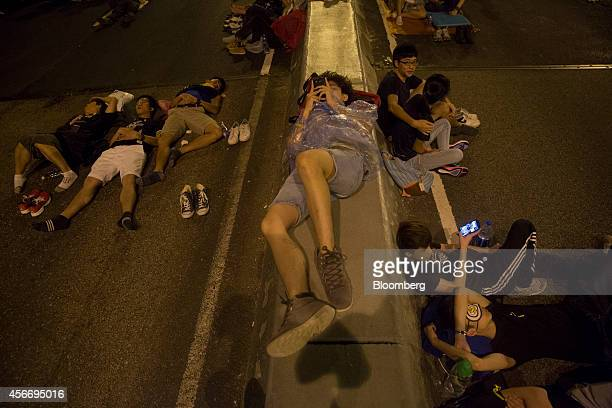 A demonstrator holds a mobile phone center near the Central Government Offices in Hong Kong China on Sunday Oct 5 2014 Student leaders of...