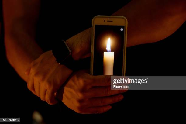 A demonstrator holds a mobile phone displaying a candle image on screen during a candlelight vigil at Victoria Park in Hong Kong China on Sunday June...