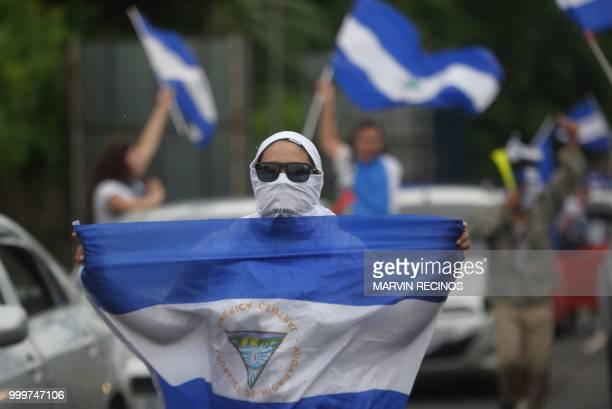 A demonstrator holds a Nicaraguan flag during the march in cars and motorcycles from Managua to Ticuantepe 15km south of Managua demanding the...