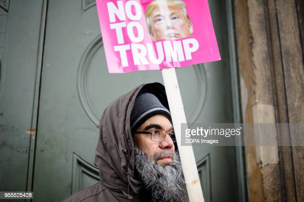 A demonstrator holds a No To Trump placard on Portland Place in freezing conditions ahead of a march against racism to mark the annual International...