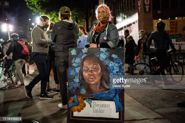 A demonstrator holds a painting of Breonna Taylor during a protest near the Seattle Police Departments East Precinct on June 7 2020 in Seattle...
