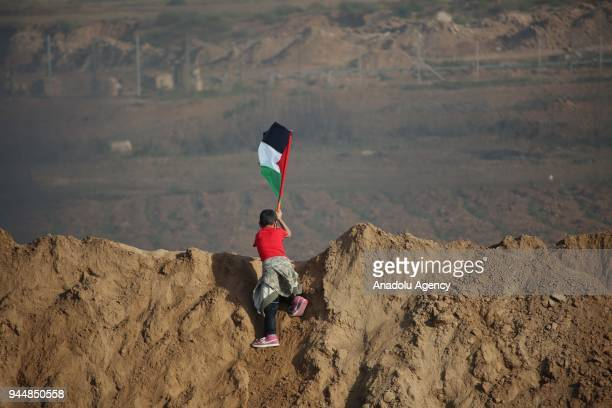 A demonstrator holds a Palestinian flag as Israeli soldiers intervene to demonstrators to remark the 'Great March of Return' at the border east of Al...