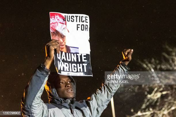 """Demonstrator holds a photo of Daunte Wright and shouts """"Don't shoot"""" at the police after curfew as people protest the death of Daunte Wright who was..."""