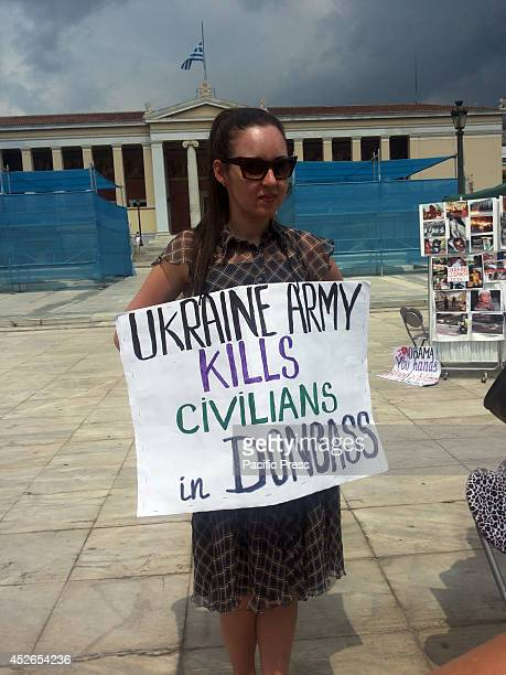 A demonstrator holds a picket with the phrase 'Ukraine Army kills civilians in Donbass People from Ukraine that live in Greece have organised a kiosk...