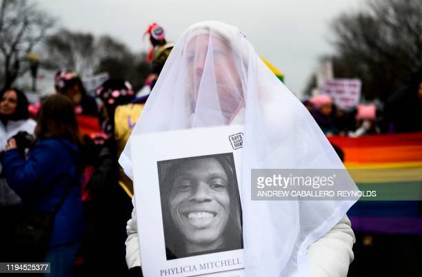 Demonstrator holds a picture of a woman killed by gun violence as she marches near the White House during the 4th annual Womens March in Washington,...