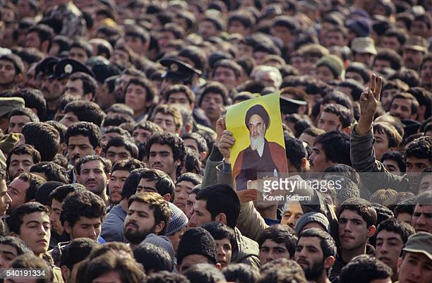 A demonstrator holds a picture of Ayatollah Khomeini during anniversary of Islamic Revolution held at Azadi square 11th February 1994 in Tehran Iran