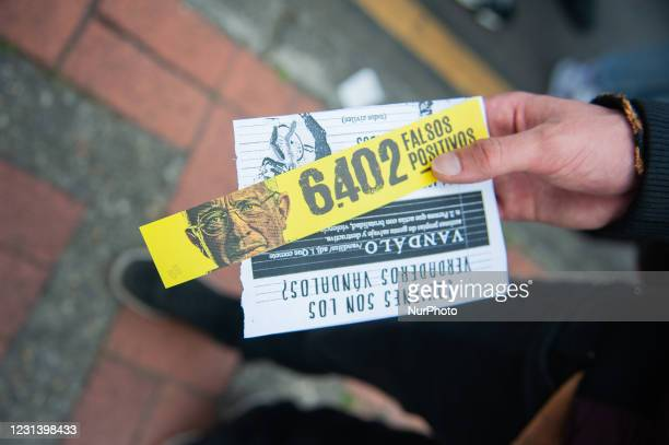 Demonstrator holds a picture of Political Figure, and Former president Alvaro Uribe with the number 6042 extrajudicial killings in demonstrations...