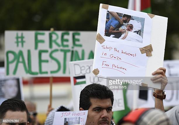 A demonstrator holds a picture showing a Palestinian child victim of an Israel's raid during a demonstration in Amsterdam on July 20 to denounce...