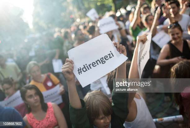 A demonstrator holds a piece of paper in her hands which reads '#direngezi' during a protest rally at the Fête de la Musique event in the Kreuzberg...