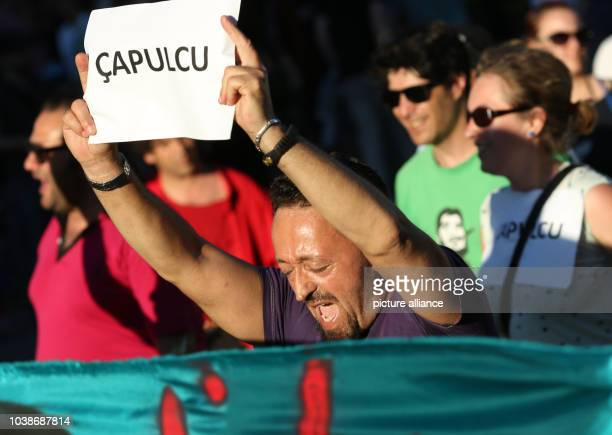 A demonstrator holds a piece of paper in his hands which reads 'Capulcu' during a protest rally at the Fête de la Musique event in the Kreuzberg...