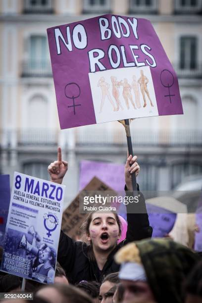A demonstrator holds a placard and shouts slongans as she protests at the Puerta del Sol square during a one day strike to defend women's rights on...