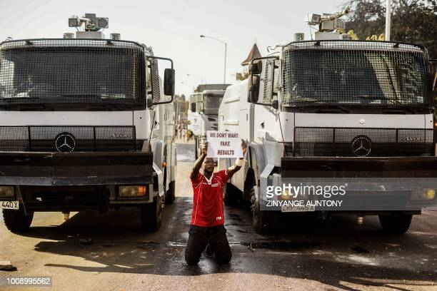 A demonstrator holds a placard as he kneels in front of police water cannons on August 1 2018 in Harare as protests erupted over alleged fraud in the...