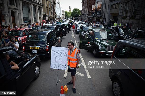 A demonstrator holds a placard as parked taxis block a street in central London during a protest by London Black Cab drivers against a new private...