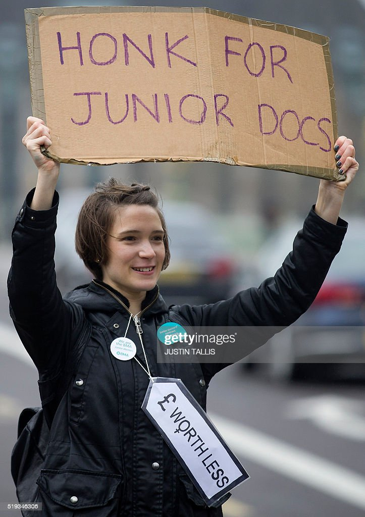 A demonstrator holds a placard as she protestests during a Junior Doctors' strike outside St Thomas' Hospital in central London on April 6, 2016, against proposed new conditions and pay rates for working unsociable hours. Thousands of operations and procedures across England have been cancelled as a result of the 48 hour strike which began Wednesday morning. / AFP / JUSTIN