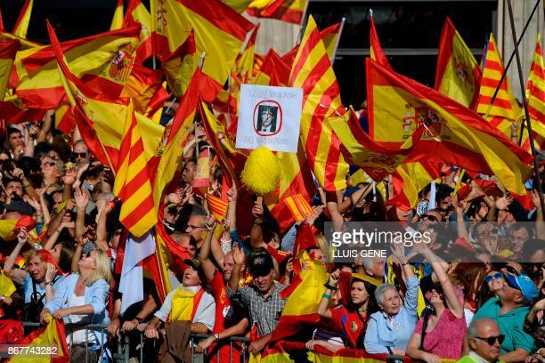 TOPSHOT A demonstrator holds a placard bearing a crossedout portrait of Catalan regional leader Carles Puigdemont who was officially ousted by Madrid...