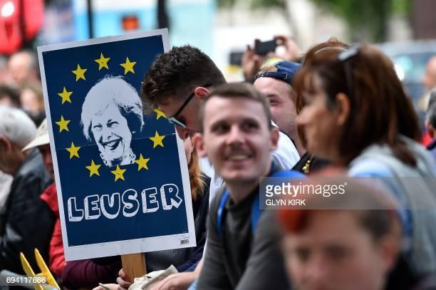 A demonstrator holds a placard depicting an image of Britain's Prime Minister Theresa May surrounded by the stars of the EU flag and with the words...