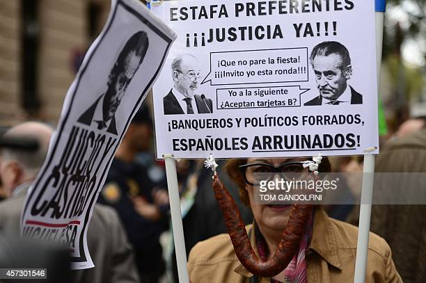 A demonstrator holds a placard depicting Former IMF head Rodrigo Rato and Caja Madrid's former head Miguel Blesa and demanding that justice be served...