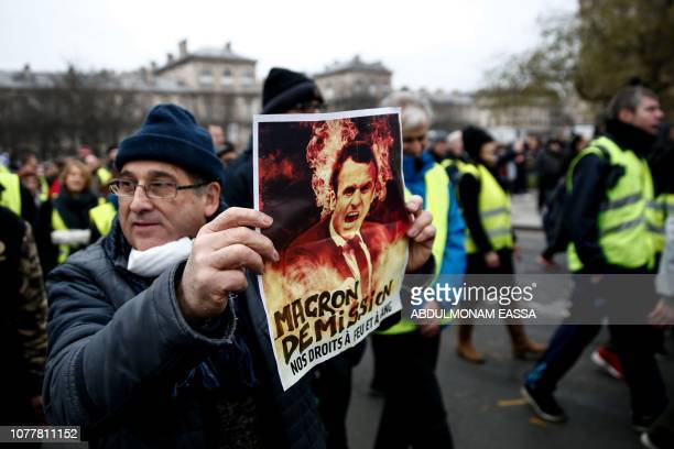 A demonstrator holds a placard displaying a picture a French President Emmanuel Macron with the words 'Macron resignation your rights with fire and...