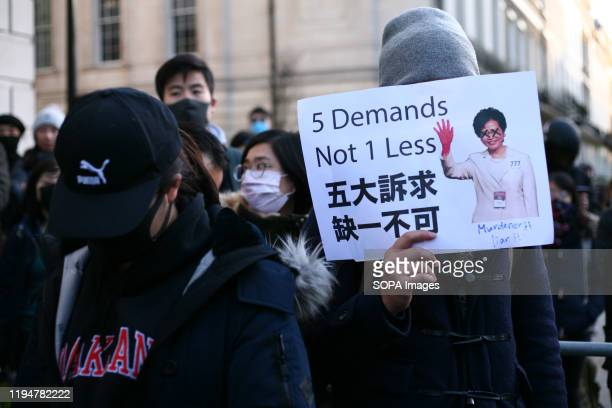 A demonstrator holds a placard featuring a picture of Hong Kong Chief Executive Carrie Lam during the protest Activists rally in solidarity with the...