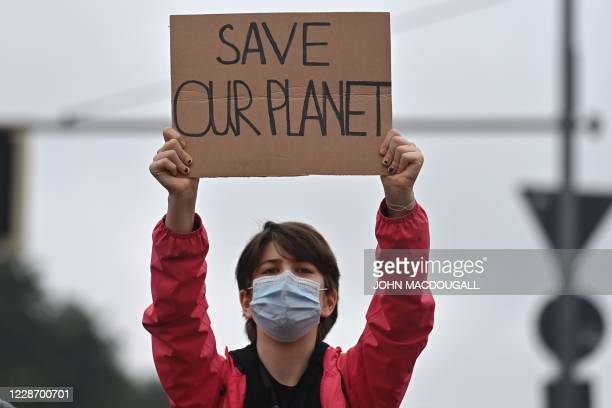 """Demonstrator holds a placard in front of the Brandenburg Gate during a demonstration of the climate activists from the """"Fridays for Future"""" movement,..."""