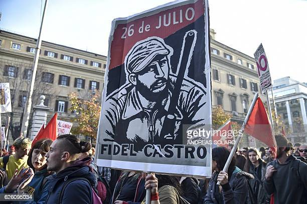 TOPSHOT A demonstrator holds a placard picturing former Cuban President Fidel Castro during a 'C'e chi dice NO' rally in central Rome on November 27...