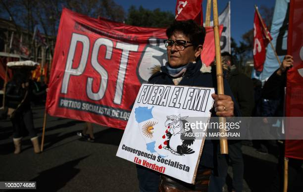 A demonstrator holds a placard reading 'IMF Out' during a protest against Argentina's latest agreement with the International Monetary Fund in Buenos...