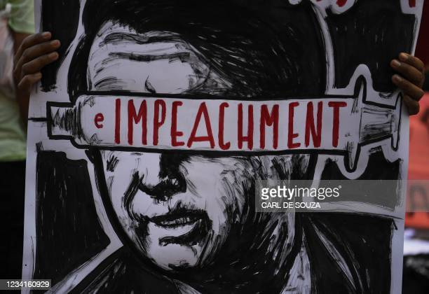 Demonstrator holds a placard reading 'Impeachment' on an image depicting Brazilian President Jair Bolsonaro during a protest against his government...