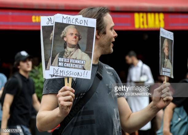A demonstrator holds a placard reading 'Macron resignation' during a demonstration on the Contrescarpe Square in Paris on July 27 where former top...