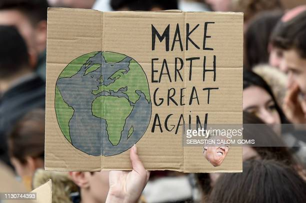 A demonstrator holds a placard reading 'Make Earth great again' during a demonstration against climate change on March 15 2019 in Nantes western...