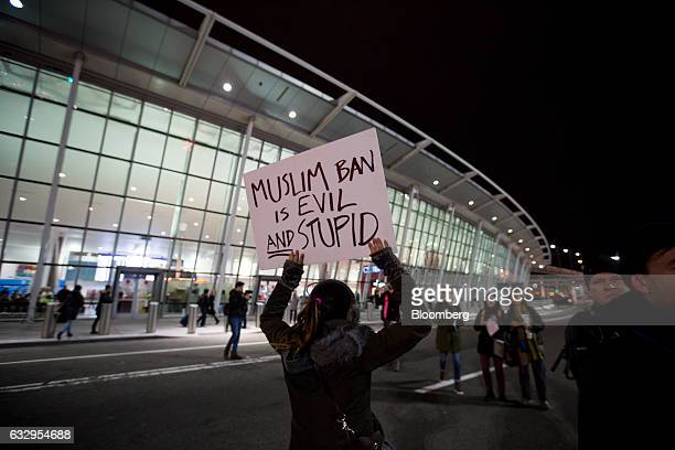 A demonstrator holds a placard reading Muslim Ban Is Evil And Stupid as she marches across a street outside Terminal 4 at John F Kennedy...