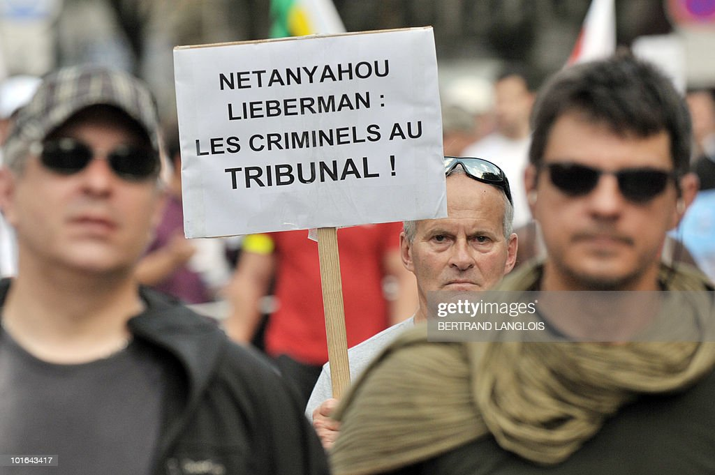 A demonstrator holds a placard reading 'Netanyahou, Lieberman : Criminals at the court' as he protests on June 5, 2010 in Paris streets against Israeli's storming of a Gaza-bound aid flotilla that left nine pro-Palestinian activits dead. The European Union will present in the coming days a proposal for lifting the Israeli blockade of Gaza, following the deadly raid this week on aid ships bound for the Palestinian territory, Spain's foreign minister said toady.